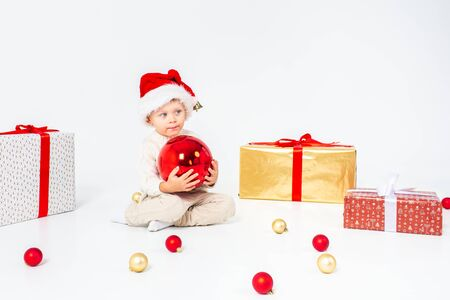 Foto de Little boy in Santas hat sitting between gifts and holding big red Christmas ball in hands. Isolated on white background. - Imagen libre de derechos