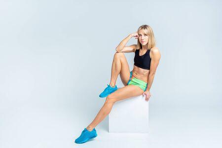 Foto für Portrait of beautiful athletic caucasian woman in sport bra and shorts sitting on a white cube on a white studio backgroung. Copyspace - Lizenzfreies Bild