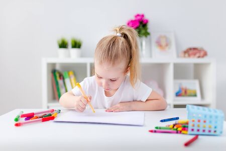 Photo pour Blonde happy little girl with ponytale drawing and writing lsitting by the white table in light roon. Preschool education, early learning. - image libre de droit