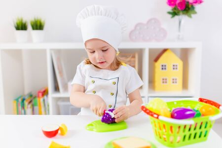 Photo pour Little blonde girl in white cook uniform playing with toy fruits and vegetables at home, in kindergaten or preschool. Game activities to play with a child at home. - image libre de droit
