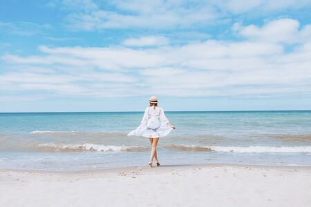 Photo for Beautiful sexy woman wearing straw hat, white swimsuit and skirt walking along the surf line on beach. Summer holidays in tropics. Copyspace. Sun protection - Royalty Free Image