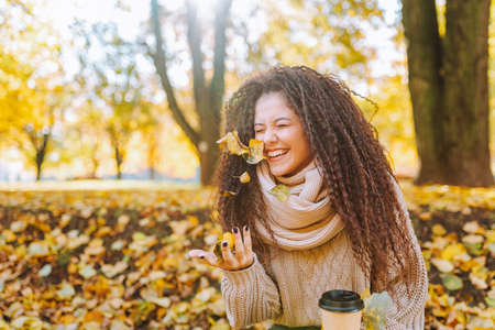 Photo pour Positive afro hair woman with beautiful smile wearing knitted sweater and scarf throw yellow autumn leaves in park on sunny day - image libre de droit
