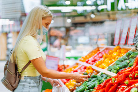Foto für Young blonde woman wearing protective mask pick fresh vegetable on stall at market. Woman buying food - Lizenzfreies Bild