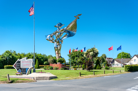 France, Normandiy, Grandcamp-Maisy: Famous French silver memorial Statue de la Paix with flags of the USA, France and Europe, park and blue sky in the background. March 08, 2015