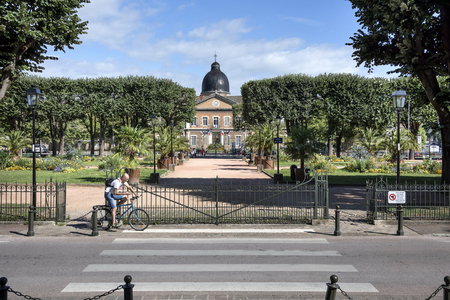 France, Bourgogne Franche Comte, Macon: Cyclist in front of famous Square de la Paix and main entrance of hospital Hotel-Dieu in the city center of the French town with blue sky. August 05, 2017
