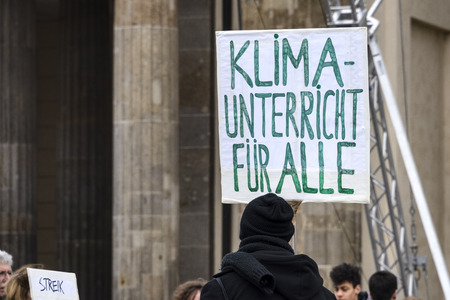 Germany, Berlin: Young pupil with 'Climate lessons for all' poster (Klimaunterricht fur alle) and people at Fridays for Future demonstration in the city center of the German capital. Mar 29, 2019