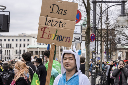 Germany, Berlin: Young pupil with 'The last Unicorn' poster (Das letzte Einhorn) and people students women at Fridays for Future demonstration in the city center of the German capital. Mar 29, 2019