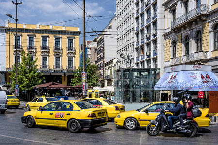 Photo for Greece, Athens, Omonia square: Street scene in the city center of the Greek capital with cars, yellow cabs, busy traffic, people, residents, shops, buildings and blue sky in background. April 26, 2018 - Royalty Free Image