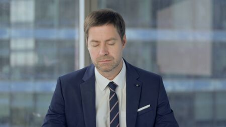 Photo for Middle Aged Businessman Sleeping While Sitting at Work - Royalty Free Image