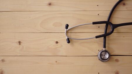 medical equipment that is seen in the image of a syringe syringe stethoscope with a wooden background