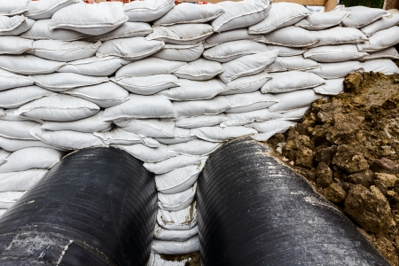 White sandbag bags are full with sand in wall formation to hold the Earth near traffic road  Industrially isolated pipes for distance heating passes under the road