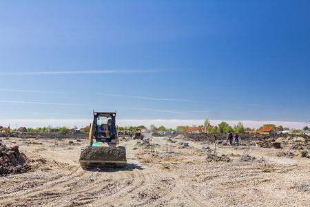 Small excavator bobcat is transport gravel in his bucket over building site.