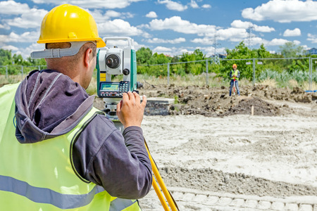 Photo for Surveyor engineer is measuring level on construction site. Surveyors ensure precise measurements before undertaking large construction projects. - Royalty Free Image