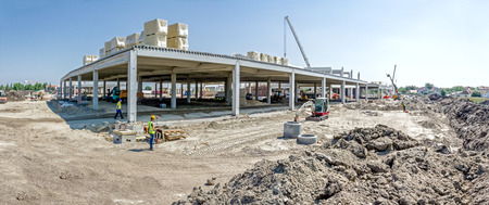 Photo pour Panorama is showing construction site with machinery, people at work. Landscape transform into large urban area, concrete hall. - image libre de droit