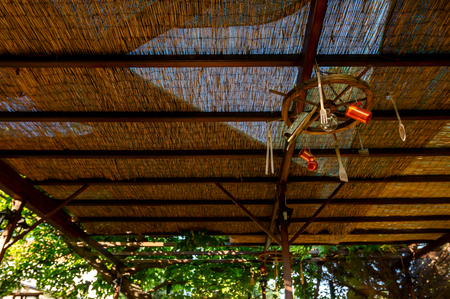Abstract scene, with wooden rudder and retro equipment for cooking hangs from the ceiling as decoration at traditional Greek tavern restaurant.