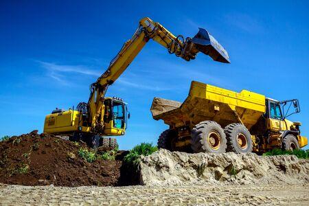 Foto de Big excavator is filling a dumper truck with soil at construction site, project in progress. - Imagen libre de derechos