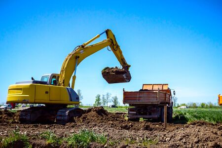Photo for Big excavator is filling a dumper truck with soil at construction site, project in progress. - Royalty Free Image