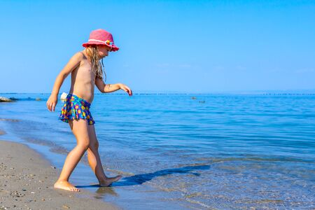 Photo pour Young woman, restless child in cute summer hat is dancing and splashing in shallow water, sandy beach at sea shore. - image libre de droit