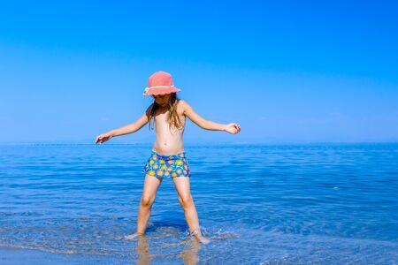 Foto de Young woman, restless child in cute summer hat is dancing and splashing in shallow water, sandy beach at sea shore. - Imagen libre de derechos