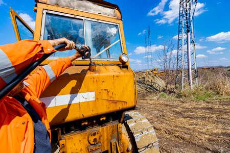 Photo pour Worker holding fuel pump gun inserted in the reservoir of construction machine, pour gasoline, diesel in the vehicle. - image libre de droit