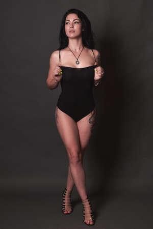 Photo pour Tattooed brunette in black swimsuit on black background - image libre de droit