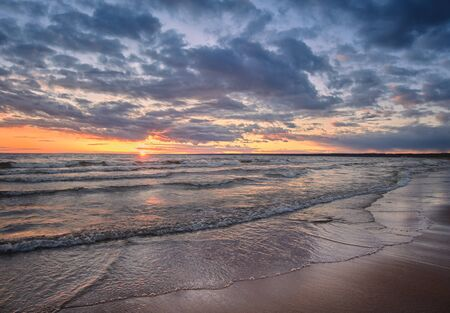 Photo for Baltic Sea panorama at sunset with shore waves and sun on the horizon. - Royalty Free Image