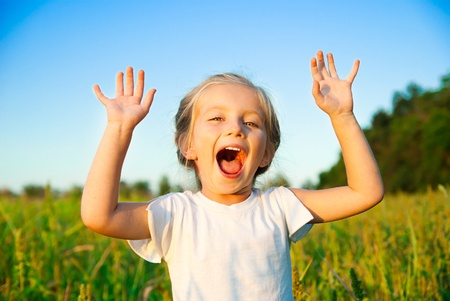little girl screaming in a meadow with hands up