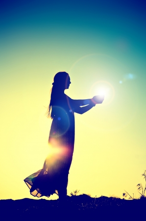 woman silhouette holding the sunの写真素材