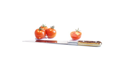 red ripe tomatoes isolated on a white background next to a knife