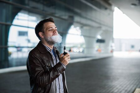 Young man enjoying a satisfying e-cigarette standing in profile against airport terminal background.