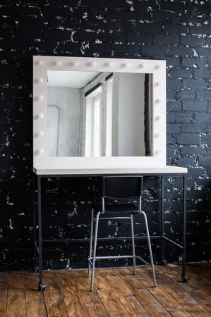 Woman's makeup place with mirror and bulbs at photo studio loft interior black brick wall.