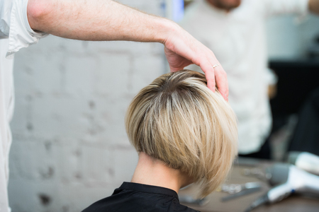 Photo for Closeup portrait teen young girl woman sitting in chair in hair salon looking in mirror while hairdresser checking her new haircut. - Royalty Free Image