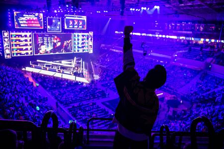 Big esports event. Video games fan on a tribune at tournaments arena with hands raised. Cheering for his favorite team.
