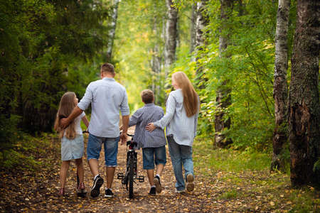 Photo for Happy family outdoors smiling in a summer forest - Royalty Free Image