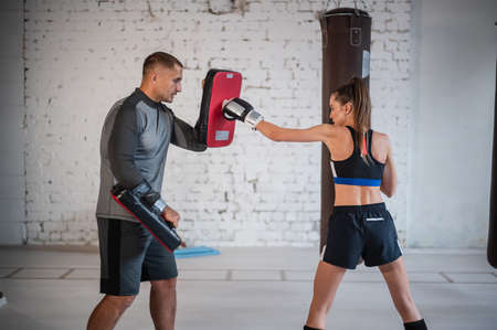 Photo pour Training fight of male and female kickboxers. Practicing kicks and strikes on the boxing paw. Working in pairs - image libre de droit