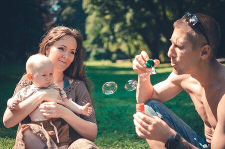 Photo pour A happy family with child resting in park - image libre de droit
