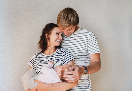Photo for Happy family portrait - parents and their little cute baby girl. Mom breastfeeding newborn kid. - Royalty Free Image