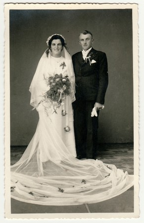 CESKY DUB, THE CZECHOSLOVAK  REPUBLIC - CIRCA 1940s: Vintage photo of newlyweds. Bride wears veil, long wedding gown and holds wedding bouquet. Groom wears black suit and white bow tie. Black & white antique studio portrait.のeditorial素材