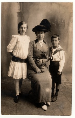 GERMANY - CIRCA 1920s: Vintage photo shows mother with her children (girl and boy). Mother wears an elegant ladies costum and feather hat, she holds the cat. Boy wears sailor costum and girl wears white dress with black sash.