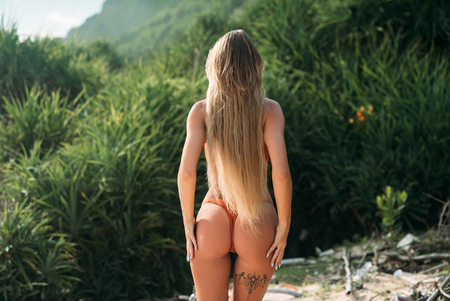 Foto de The view from the back is a sexy girl with white long hair that touch the priests standing in a bikini and put her hands on her hips. Beautiful round ass model on the beach. - Imagen libre de derechos