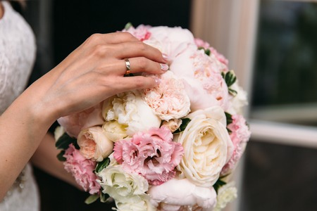 Photo pour Close-up of a cropped frame, the hand of a young girl with an engagement ring on a ring finger. Gently touches the wedding bouquet of peonies. Wedding day, bouquet of the bride. wedding ring - image libre de droit