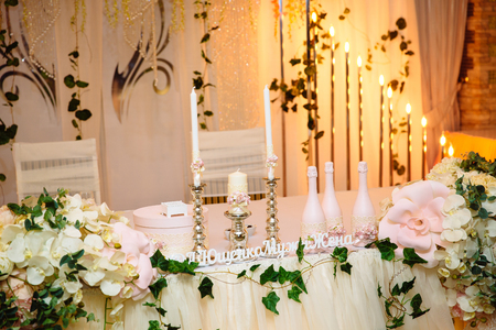 The concept of a wedding celebration, celebration of lovers, decor, flowers, fabrics. The table of the newlyweds is decorated with flowers, candles and fabrics