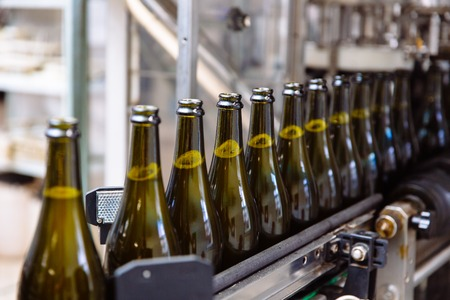 Photo pour Glass bottles on the automatic conveyor line at the champagne or wine factory. Plant for bottling alcoholic beverages. - image libre de droit