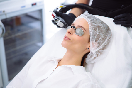 Photo pour Close-up cosmetologist makes a laser treatment to young woman face, hair removal epilation procedures at beauty SPA clinic. - image libre de droit