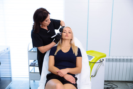 A cosmetologist carries out procedures for manipulating the hydropeeling apparatus on a woman face.