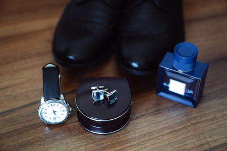 Foto de Mens leather shoes, watches and cufflinks on the background of a brown table. Clothing accessories businessman. Concept of grooms accessories at wedding day. - Imagen libre de derechos