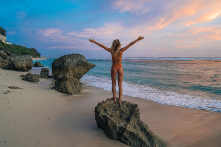Photo pour Backside veiw slender girl in swimwear with wide open arms stands on beach, looks at ocean and beautiful sunset - image libre de droit