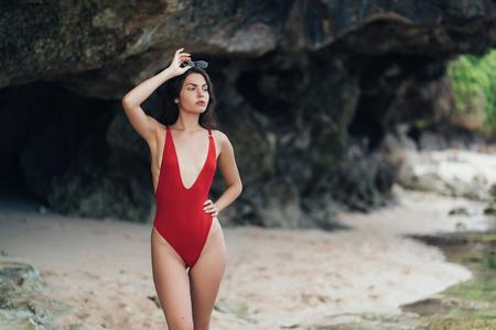 Foto de Portrait of sexy model in red swimwear and sunglasses posing on rocky beach - Imagen libre de derechos