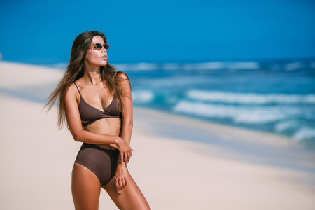Photo pour Sexy tanned model with sunglasses in brown swimsuit posing on white sandy beach - image libre de droit