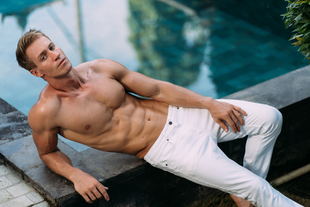 Photo pour Sexy fitness man in  white pants with sporty body sits near swimming pool - image libre de droit